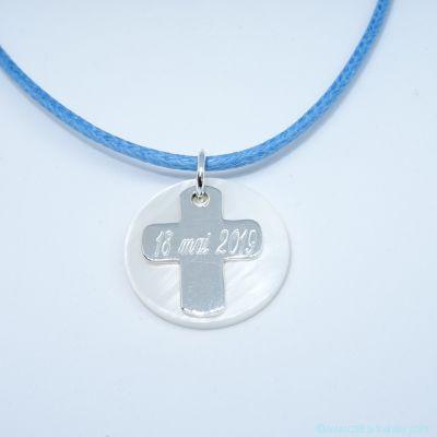 La croix gravée en argent et sa pastille de nacre, sur cordon