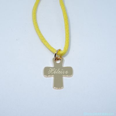 La croix fine en plaqué or sur cordon