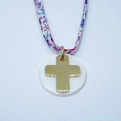 La croix gravée en plaqué or et sa pastille de nacre, sur Liberty